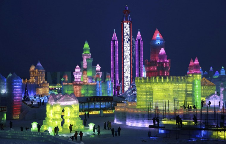 People visit newly-built ice sculptures illuminated by coloured lights during a trial operation of the 16th Harbin Ice and Snow World in Harbin, Heilongjiang province, December 22, 2014. The annual Harbin Ice and Snow World will be officially opened on January 5, 2015. Picture taken December 22, 2014. (REUTERS/Stringer)