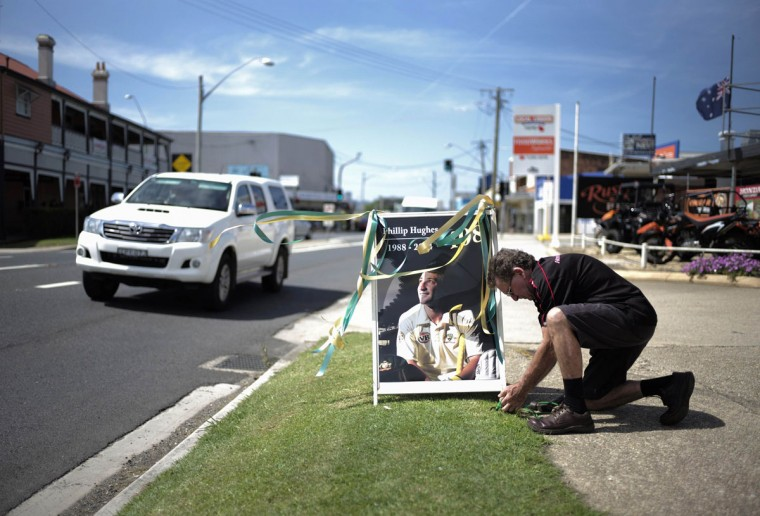 A hardware store employee displays a tribute to deceased Australian cricketer Phillip Hughes in Macksville, as his hometown prepares for his funeral, December 2, 2014. Hughes died last Thursday, two days after he was struck in the head by a short-pitched delivery during a first class game at the Sydney Cricket Ground. (REUTERS/Jason Reed)