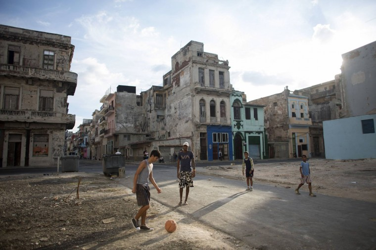 People play soccer on the street in downtown Havana, December 22, 2014. From bus drivers to bartenders and ballet dancers, many Cubans are already imagining a more prosperous future after the United States said it will put an end to 50 years of conflict with the communist-run island. (REUTERS/Alexandre Meneghini)