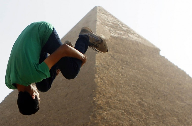 """Faisel,16, a member of Egyptian parkour group """"EGY PK"""", practices a jump in front of the Pyramid of Khufu, the largest of the Great Pyramids of Giza, on the outskirts of Cairo. EGY PK, one of the first parkour groups in Egypt, are training ahead of performing publicly during the year-end Christmas celebrations, to promote tourism in Egypt. Egypt's tourism revenues jumped 112 percent to about $2 billion in the third quarter of 2014, a tourism ministry official said, suggesting the key industry was showing signs of recovery, albeit from a particularly bad third quarter last year. Tourism, an important source of foreign currency, has been hammered since the popular uprising that toppled Hosni Mubarak in 2011. (Amr Abdallah Dalsh/Reuters photo)"""