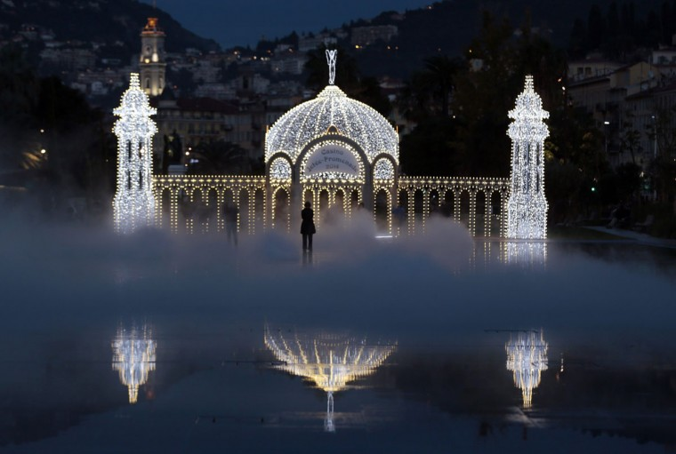 People stand in the mist as they look at a replica of the casino along the Promenade jetty as part of the Christmas holiday illuminations in Nice December 16, 2014. (REUTERS/Eric Gaillard)