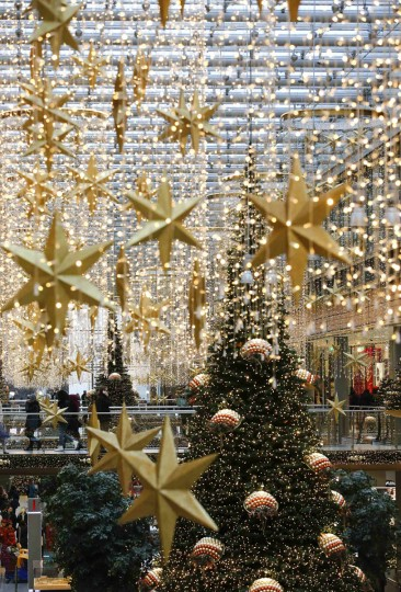 People walk in a shopping mall decorated with Christmas lights in Berlin, December 19, 2014. (Fabrizio Bensch/Reuters)