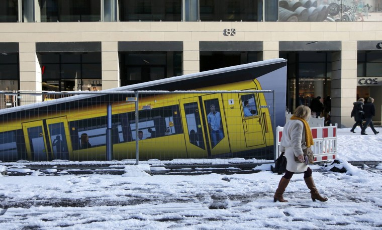 People walk beside a painted U-Bahn underground train marking an entrance of the new Unter den Linden underground station currently under construction in Berlin, December 29, 2014. (Fabrizio Bensch/Reuters)