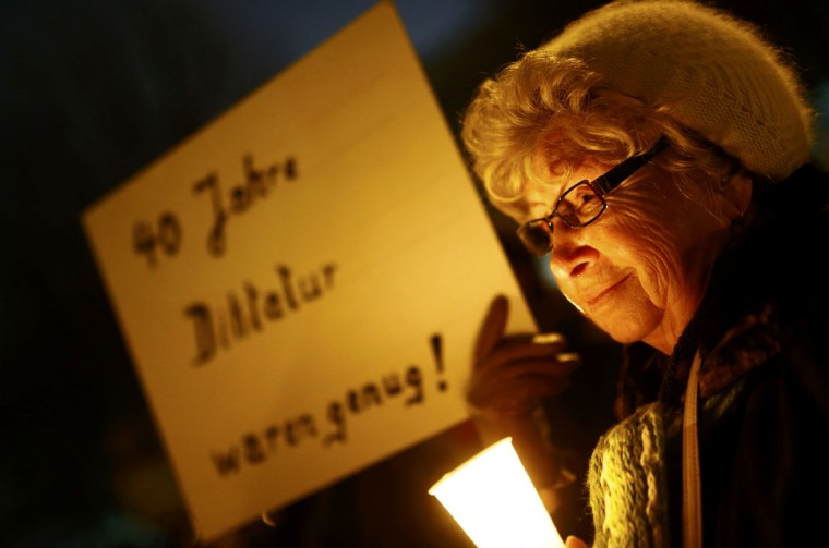 An elderly woman demonstrates against the prospect of Bodo Ramelow of the Left party (Die Linke) becoming Thuringia state premier and leading a state coalition with the Social Democrats (SPD) and Greens, during a protest rally in Erfurt December 4, 2014. The Cold War has flared up again in Germany ahead of a tight and unpredictable state assembly vote on Friday in the eastern state of Thuringia, where the reform communist Left party is yearning to take control of a regional government for the first time. The SPD and Greens have been accused of betraying victims of East Germany's communist dictatorship by cooperating with the Left, which is popular in the east and traces its roots to the Socialist Unity Party of Germany that built the Berlin Wall. Placards reads '40 years of dictatorship was enough' REUTERS/Kai Pfaffenbach