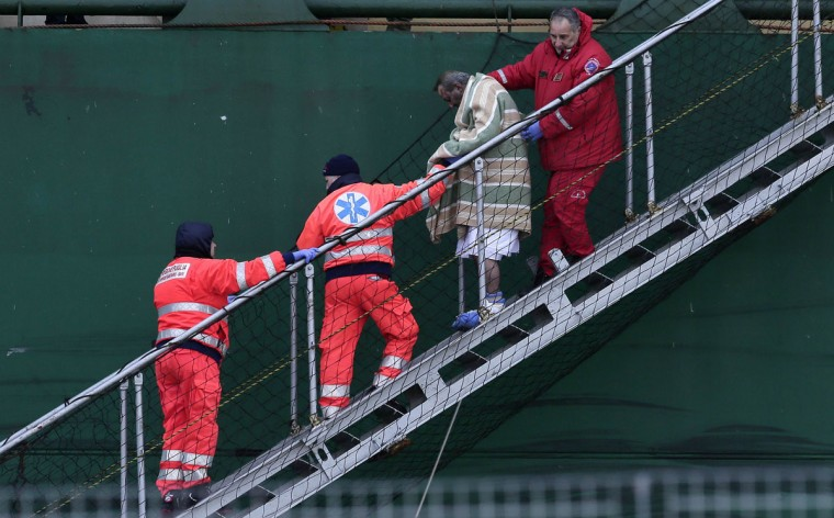 "A wounded passenger is helped as he leaves from the "" Spirit of Piraeus "" cargo container ship at Bari harbour, after the car ferry Norman Atlantic caught fire in waters off Greece December 29, 2014. Rescue teams working through the night have pulled 265 people off a stricken car ferry which caught fire off the coast of Greece but more than 200 are stranded on board, the Italian navy said on Monday. (Yara Nardi/Reuters)"