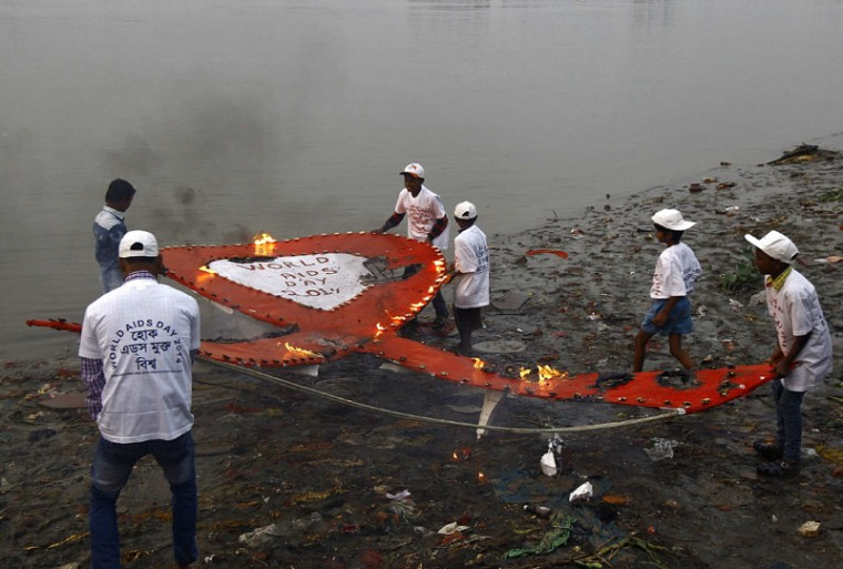 "Activists from a non-governmental organization (NGO) carry a giant red ribbon lit with oil lamps before releasing it in the waters of the river Ganges during an HIV/AIDS awareness campaign to mark World AIDS Day in Kolkata December 1, 2014. The world has finally reached ""the beginning of the end"" of the AIDS pandemic that has infected and killed millions in the past 30 years, according to a leading campaign group fighting HIV. United Nations data show that in 2013, 35 million people were living with HIV, 2.1 million people were newly infected with the virus and some 1.5 million people died of AIDS. By far the greatest part of the HIV/AIDS burden is in sub-Saharan Africa. (Rupak De Chowdhuri/Reuters)"