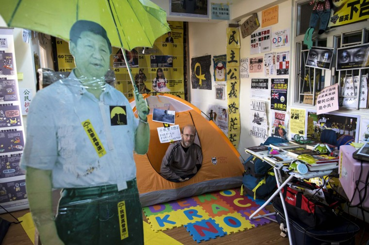 "An Occupy-themed guesthouse run by British freelance writer Stephen Thompson, 50, is pictured as he poses in his tent in Hong Kong December 30, 2014. Set up in a small apartment in the Causeway Bay shopping district, the guesthouse that gives what it calls ""Umbrella Revolution Occupation Experience"" charges guest HK$100 (US$13) a night to stay in a tent surrounded by pro-democracy banners, a cardboard cutout of Chinese President Xi Jinping holding a yellow umbrella, and serves toilet paper printed with the face of embattled leader of Hong Kong chief executive Leung Chun-ying. (Tyrone Siu/Reuters)"