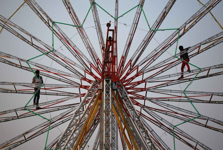 Workers install lights while standing on a ferris wheel at a fair in Mumbai December 8, 2014. (Danish Siddiqui/Reuters)