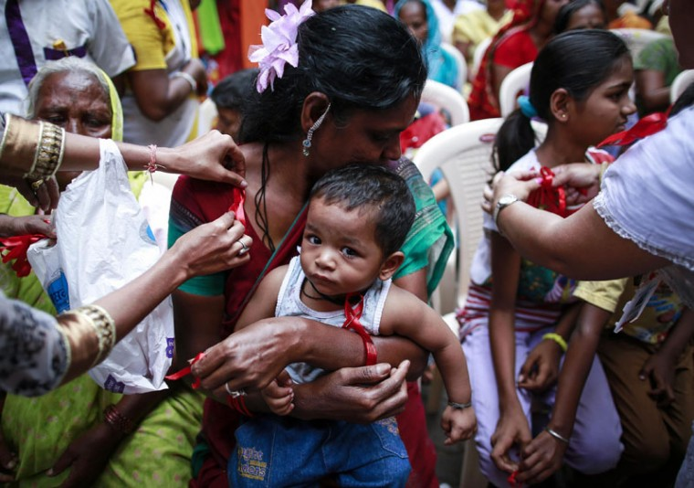 A volunteer pins a red ribbon on the blouse of a sex worker, as her child looks on, during an event to mark World AIDS Day in Kamathipura, Mumbai's red light district, December 1, 2014. The event was organized by the Social Activities Integration, a non-profit organization which provides free condoms and medical care to people living with HIV and AIDS. (Danish Siddiqui/Reuters)