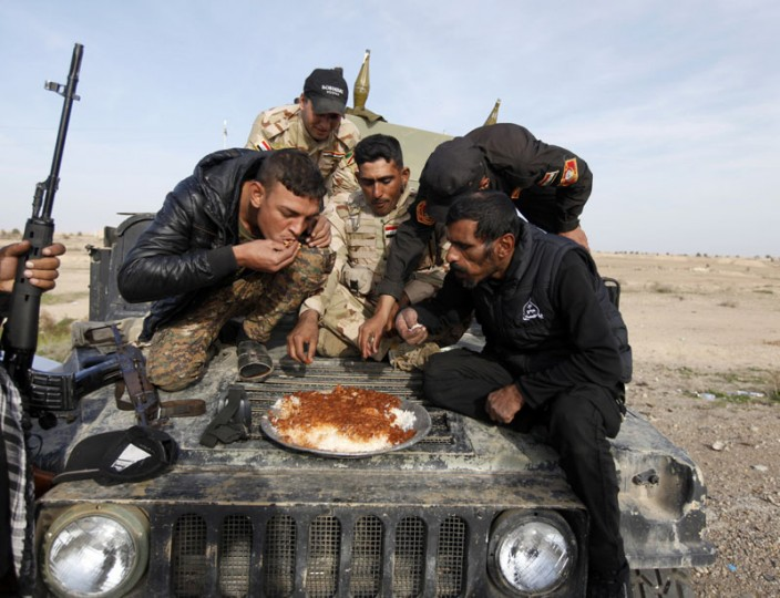 Members of Iraqi security forces and Shiite fighters eat on their vehicle on the outskirts of Baiji, north of Baghdad December 8, 2014. (Ahmed Saad/Reuters)