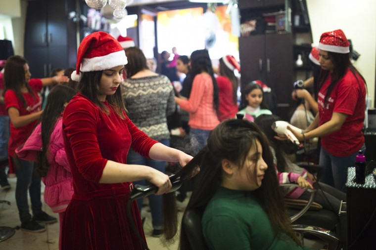 A Palestinian hairstylist wearing a Santa Claus hat straightens the hair of a customer in a salon at Jerusalem's Old City December 19, 2014. (Amir Cohen/Reuters)