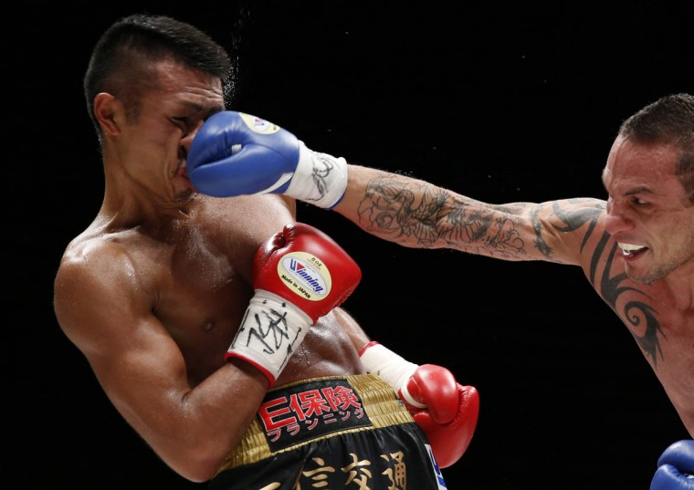 Challenger Israel Perez of Argentina punches the champion Takashi Uchiyama (Left) of Japan during their WBA boxing super featherweight title bout in Tokyo December 31, 2014. Uchiyama won the match by technical knock out in the ninth round. (Yuya Shino/Reuters photo)