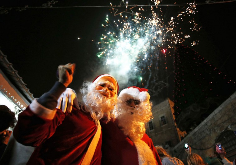 People wearing Santa Claus outfits attend a Christmas tree lighting ceremony at Jerusalem's Old City December 19, 2014. (Ammar Awad/Reuters)