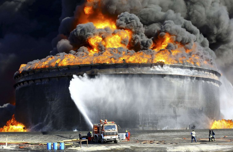 Firefighters work to put out the fire of a storage oil tank at the port of Es Sider in Ras Lanuf December 29, 2014. Oil tanks at Es Sider have been on fire for days after a rocket hit one of them, destroying more than two days of Libyan production, officials said on Sunday. Libya has appealed to Italy, Germany and the United States to send firefighters. (Stringer/Reuters)