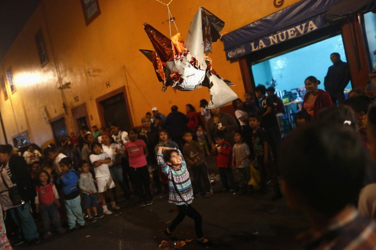 "A girl prepares to hit a pinata during a traditional Mexican Christmas celebration known as ""Posada mexicana"" at La Merced neighbourhood in Mexico City December 17, 2014. Posada Mexicana is a pre-Christmas celebration to commemorate the journey of the Holy Family from Galilee to Bethlehem. Picture taken December 17, 2014. REUTERS/Edgard Garrido"