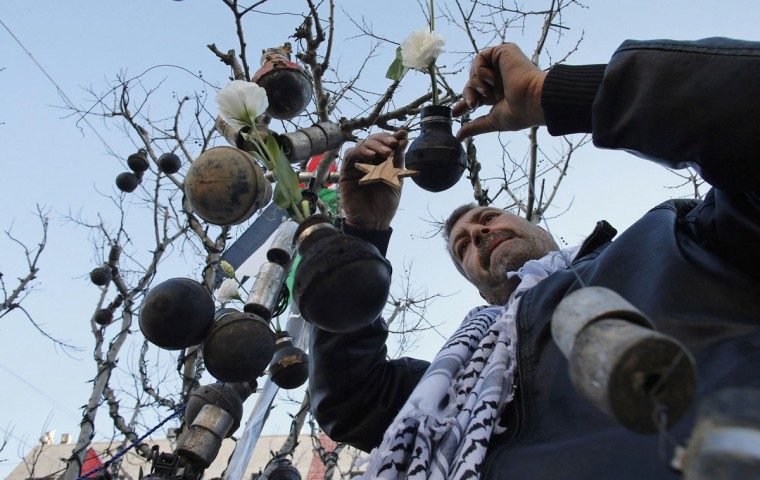 A Palestinian man decorates a tree with spent tear gas canisters that he said were fired by Israeli troops during clashes with Palestinian protesters, at Manger Square, ahead of Christmas, in the West Bank city of Bethlehem December 23, 2014. (REUTERS/Ammar Awad)