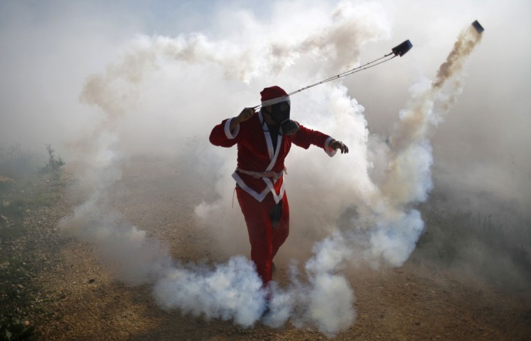 A Palestinian protester, dressed as Santa Claus, uses a slingshot to return a tear gas canister fired by Israeli troops during clashes following a demonstration against Jewish settlements in the West Bank village of Bilin, near Ramallah December 26, 2014. REUTERS/Mohamad Torokman