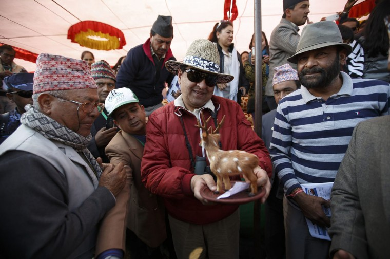 "Nepal's former King Gyanendra Bir Bikram Shah Dev (C) looks at a token presented to him during the Elephant Festival event at Sauraha in Chitwan, about 170 km (106 miles) south of Kathmandu December 30, 2014. Elephants and ""mahouts,"" or elephant riders, from Chitwan are participating in the Elephant festival, which involves elephant races, elephants playing an exhibition soccer match and taking part in various other sporting activities. The event runs from December 26 to December 30. (Navesh Chitrakar/Reuters)"