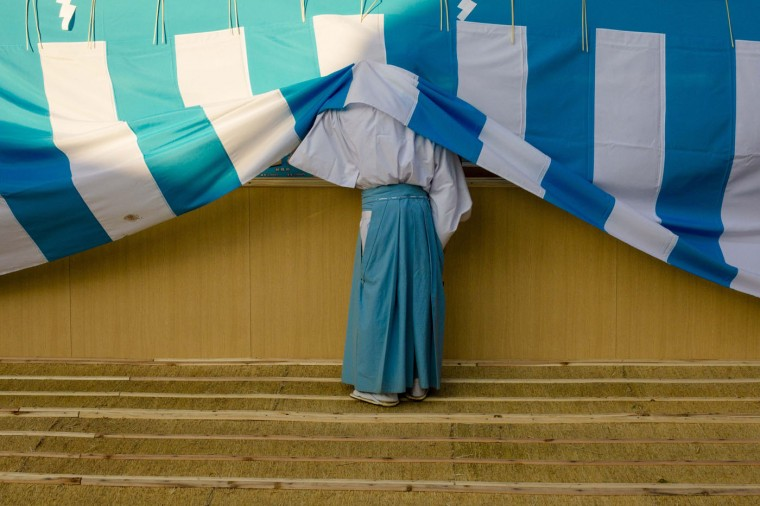 A Shinto priest looks behind a cover during ceremonies bidding farewell to 2014, ahead of New Year's Day, at the Meiji Shrine in Tokyo December 31, 2014. REUTERS/Thomas Peter