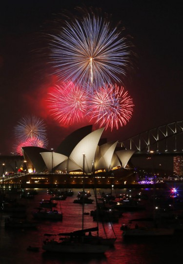 Fireworks light up the Sydney Opera House and Harbour Bridge during an early light show before the midnight New Year fireworks, December 31, 2014. More than 10,000 aerial fireworks, 25,000 shooting comets and 100,000 pyrotechnic effects are expected to be used during the annual Sydney Harbour New Year's Eve show, with an estimated 1.6 million people watching from along the harbour foreshore, local media reported. REUTERS/Jason Reed