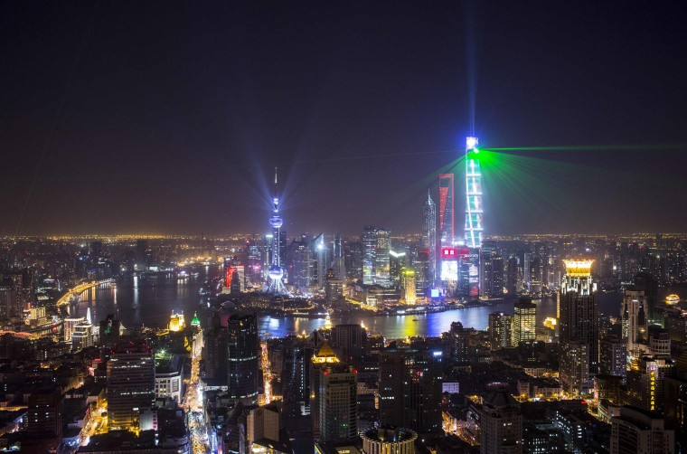 Light and laser illuminate the Lujiazui financial district of Pudong in Shanghai during a light show as part of a New Year countdown celebration on the Bund in Shanghai January 1, 2015. REUTERS/Aly Song