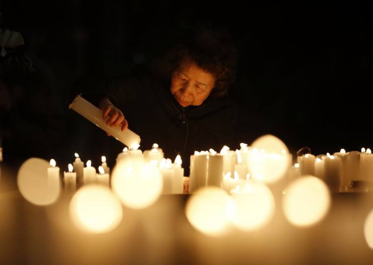 A woman lights a candle before a ceremony to celebrate the new year at Bongeun Buddhist temple in Seoul December 31, 2014. REUTERS/Kim Hong-Ji