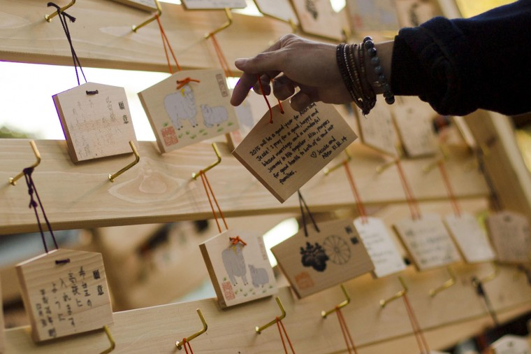 """A man hangs an """"Ema"""", a wooden plaque with people's wishes or prayers, on a hook during ceremonies bidding farewell to 2014, ahead of New Year's Day, at the Meiji Shrine in Tokyo December 31, 2014. REUTERS/Thomas Peter"""