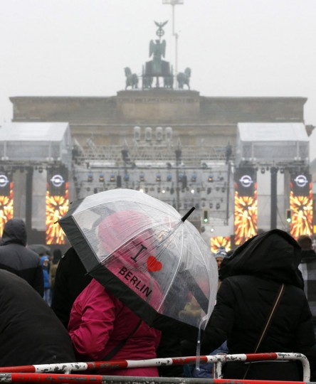 A woman uses an umbrella to protect herself from rain during New Year celebrations at the Brandenburger Tor gate in Berlin December 31, 2014. REUTERS/Fabrizio Bensch