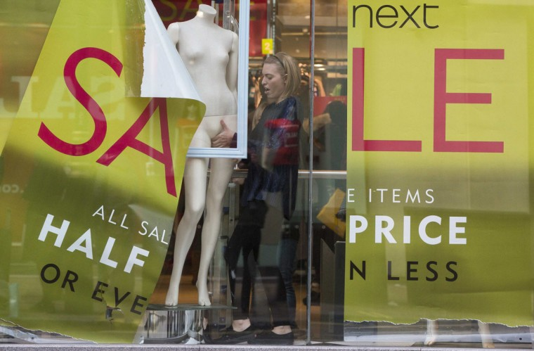 A shop assistant creates a window display in a Next store in central London December 30, 2014. British clothing retailer Next's sales rose 2.9 percent in the run up to Christmas mostly due to online and catalogue purchases, hitting the upper end of its predictions and it said full-year profit would rise by about 11.5 percent. (Neil Hall/Reuters)