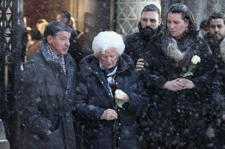 Elise Beliveau (Center) looks down at her white rose following the funeral of her husband, Montreal Canadiens hockey legend Jean Beliveau, at Mary Queen of the World Cathedral in Montreal Beliveau, a Hall of Fame ice hockey player who won 10 Stanley Cup championships with the National Hockey League's Montreal Canadiens, died on December 2 at the age of 83. (Christinne Muschi/Reuters photo)