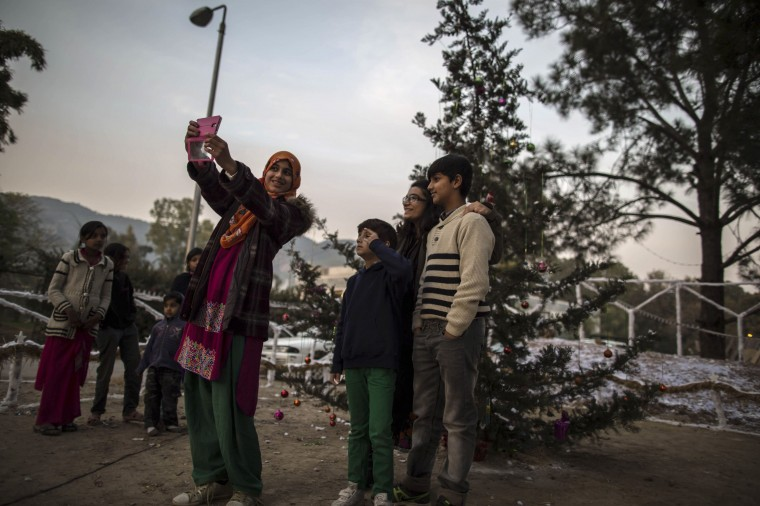 Muslims take a selfie near a Christmas tree ahead of Christmas in a Christian slum in Islamabad December 24, 2014. REUTERS/Zohra Bensemra