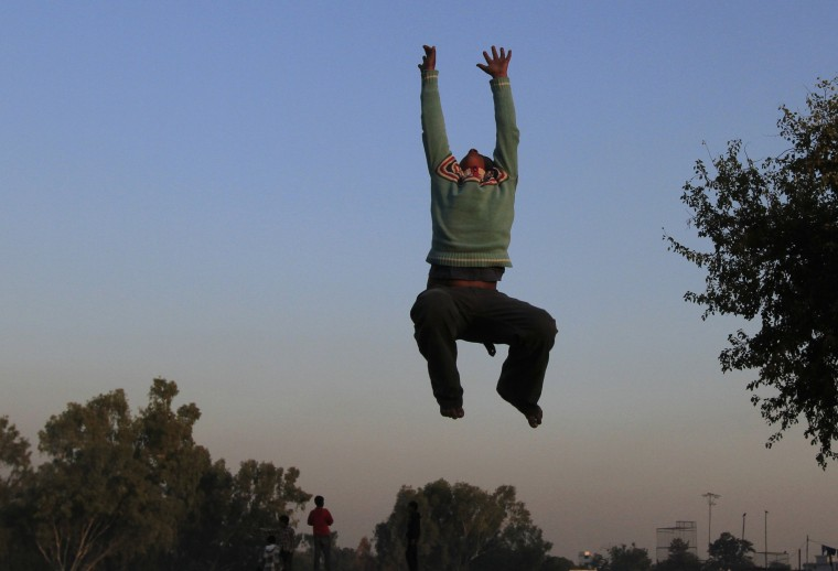 A boy jumps on a trampoline as he plays at a Christian slum in Islamabad December 10, 2014. REUTERS/Faisal Mahmood