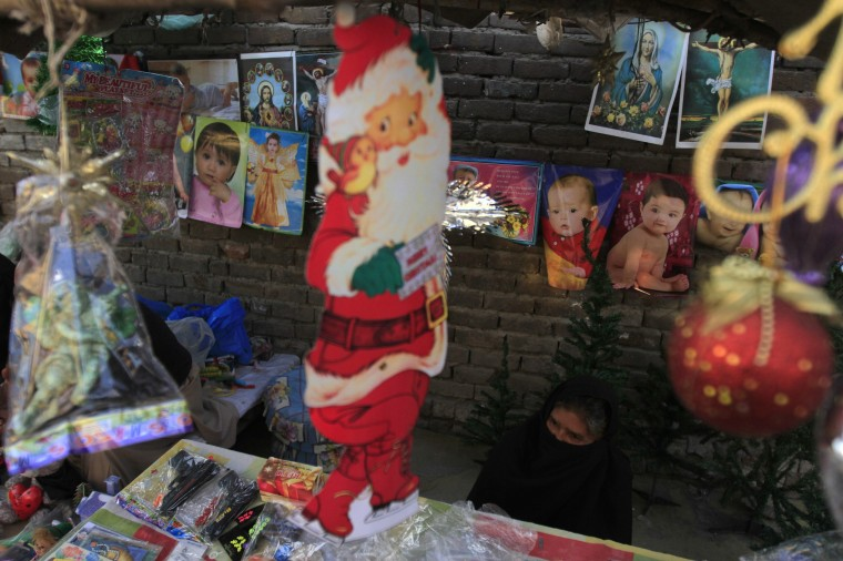 A picture of Santa Claus is displayed at a stall as a woman waits for customers at a Christian slum in Islamabad December 10, 2014. REUTERS/Faisal Mahmood
