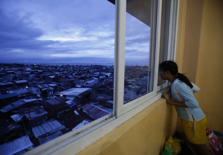 A girl looks out of a window as rain clouds cover the sky, at an evacuation centre for the coastal community, to shelter from typhoon Hagupit, in Manila, December 8, 2014. Hundreds of thousands of Filipinos began to return to their homes battered by a powerful typhoon at the weekend, but the nation collectively breathed a sigh of relief as a massive evacuation plan appeared to minimize fatalities. (Cheryl Gagalac/Reuters)