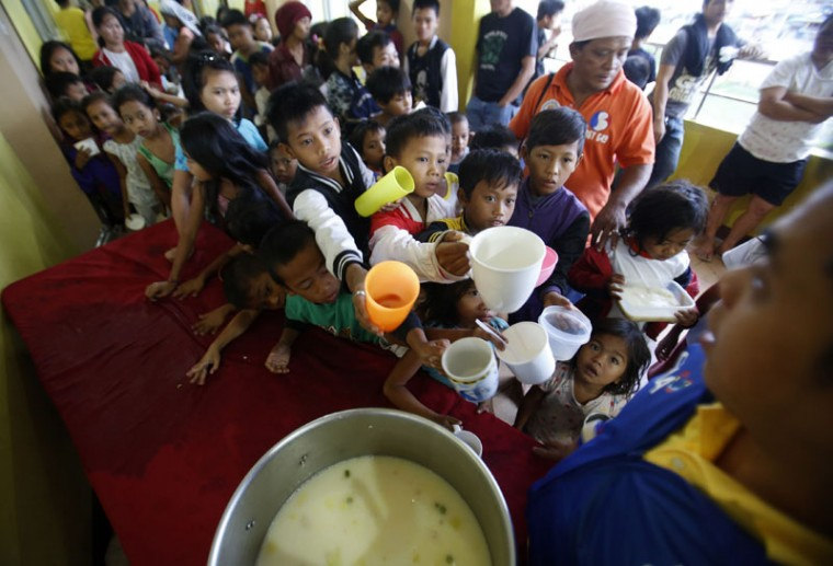 Children queue for food at an evacuation centre for the coastal community, to shelter from typhoon Hagupit, near Manila, December 8, 2014. Hundreds of thousands of Filipinos began to return to their homes battered by a powerful typhoon at the weekend, but the nation collectively breathed a sigh of relief as a massive evacuation plan appeared to minimize fatalities. (Cheryl Gagalac/Reuters)