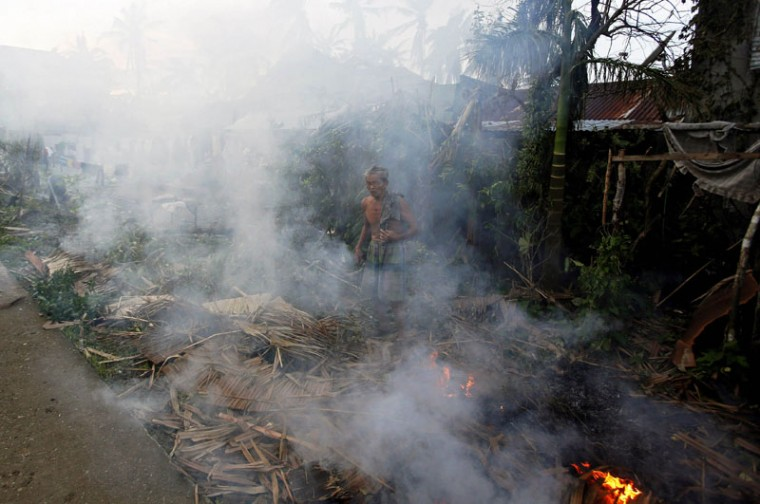 A resident burns debris brought at the height of Typhoon Hagupit in Dolores, Samar, in central Philippines December 8, 2014. At least 21 people were reported dead, many of them drowned as flood waters rose in Borongan, the main town in Eastern Samar, where typhoon Hagupit made first landfall, the Philippine National Red Cross said on Monday. The Philippines had evacuated more than a million people as the powerful typhoon approached the country from the Pacific, fearing a repeat of a super storm last year that left more than 7,000 dead or missing. (Erik De Castro/Reuters)