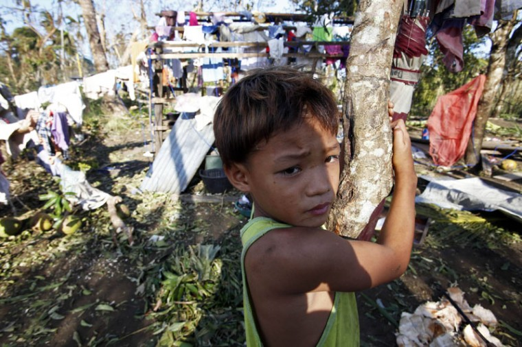 A typhoon victim stands near clothes hung out for drying in Dolores, Samar, in central Philippines December 8, 2014. At least 21 people were reported dead, many of them drowned as flood waters rose in Borongan, the main town in Eastern Samar, where typhoon Hagupit made first landfall, the Philippine National Red Cross said on Monday. The Philippines had evacuated more than a million people as the powerful typhoon approached the country from the Pacific, fearing a repeat of a super storm last year that left more than 7,000 dead or missing. (Erik De Castro/Reuters)