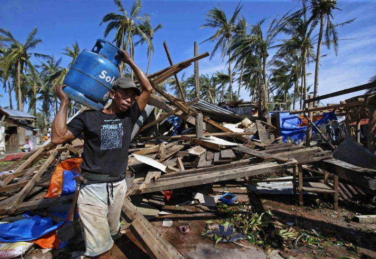 A typhoon victim carries a gas tank for cooking past a house destroyed by Typhoon Hagupit in Borongan city, Samar, in central Philippines December 8, 2014. At least 21 people were reported dead, many of them drowned as flood waters rose in Borongan, the main town in Eastern Samar, where typhoon Hagupit made first landfall, the Philippine National Red Cross said on Monday. The Philippines had evacuated more than a million people as the powerful typhoon approached the country from the Pacific, fearing a repeat of a super storm last year that left more than 7,000 dead or missing. (Erik De Castro/Reuters)