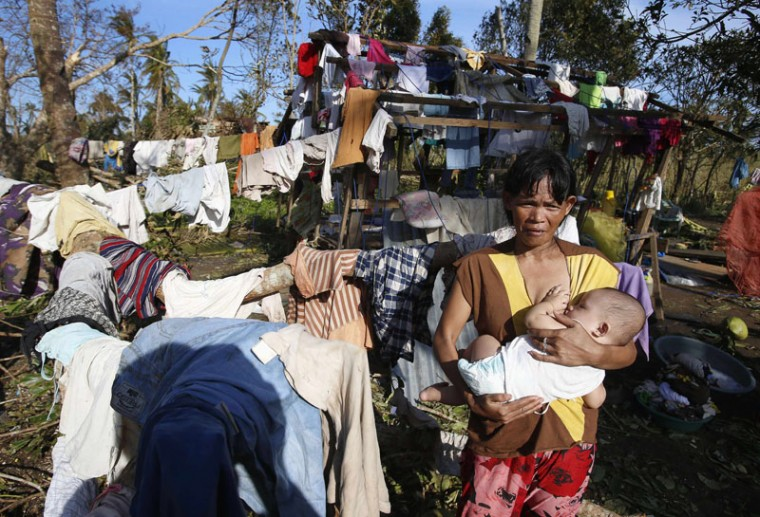 A typhoon victim carries her baby near clothes hung out for drying in Dolores, Samar, in central Philippines December 8, 2014. At least 21 people were reported dead, many of them drowned as flood waters rose in Borongan, the main town in Eastern Samar, where typhoon Hagupit made first landfall, the Philippine National Red Cross said on Monday. The Philippines had evacuated more than a million people as the powerful typhoon approached the country from the Pacific, fearing a repeat of a super storm last year that left more than 7,000 dead or missing. (Erik De Castro/Reuters)