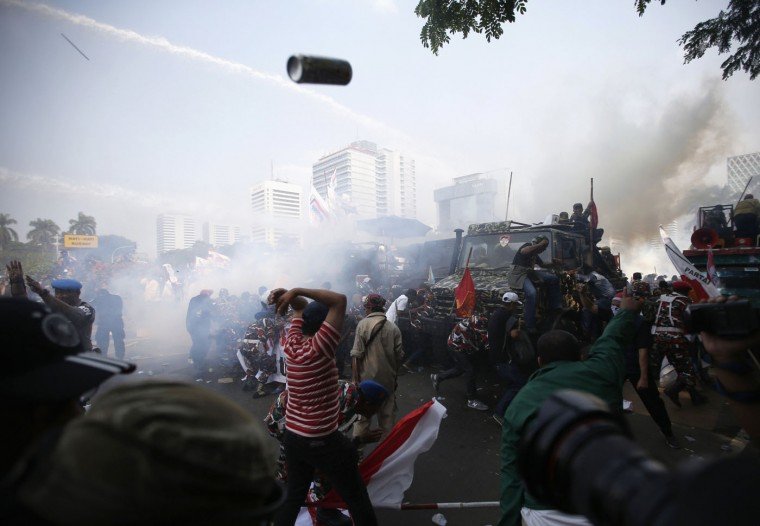 Indonesian police use tear gas and water cannon to disperse supporters of presidential candidate Prabowo Subianto in Jakarta in this August 21, 2014 file photo. After Prabowo supporters had been taunting the police who were holding the barricade, the police launched a very quick and violent strike to disperse them. I had a helmet on so I was able to stand my ground for a few seconds while sticks, rocks and teargas flew through the air - added to that I had attack dogs right behind me. The clash was fast and decisive. The supporters were not expecting such a violent reaction and dispersed. It was all over in a few minutes. - Darren Whiteside