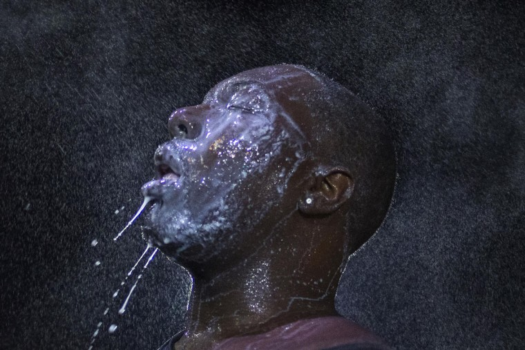 A man is doused with milk and sprayed with mist after being hit by an eye irritant from security forces in Ferguson, Missouri in this August 20, 2014 file photo. As the evening rolled past midnight, I saw one man among the crowd who looked particularly agitated. He seemed to be a local resident, very upset with the police, and people were holding him back as he yelled towards the officers. As he kept shouting, the police targeted him with some kind of eye irritant it looked like pepper spray. He wasn't very close, but they got him right in the eye and his friends immediately pulled him to a parking lot nearby, where they poured milk on his face to flush away the effects of the spray. As they started to pour the milk, I began photographing and noticed a bright spotlight in the background. I believe it was from the police. At that point the people taking care of the man started spraying mist or water to further clear his eyes and I positioned my camera and used the light source to create a rim light around his head and bring attention to the droplets. - Adrees Latif