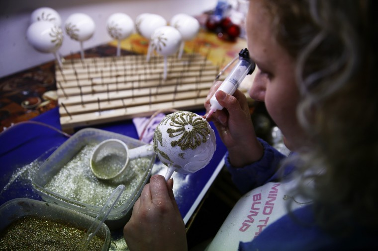 A worker paints Christmas decorations on glass baubles at the Silverado manufacture of hand-blown Christmas ornaments in the town of Jozefow, outside Warsaw December 2, 2014. REUTERS/Kacper Pempel