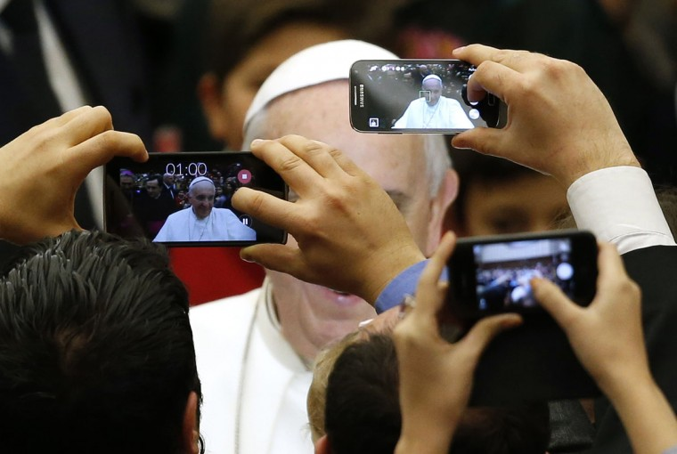 Pope Francis is pictured by mobile phones as he arrives to lead a special audience for Vatican employees and their families at the Paul VI's hall at the Vatican December 22, 2014. (Alessandro Bianchi/Reuters)