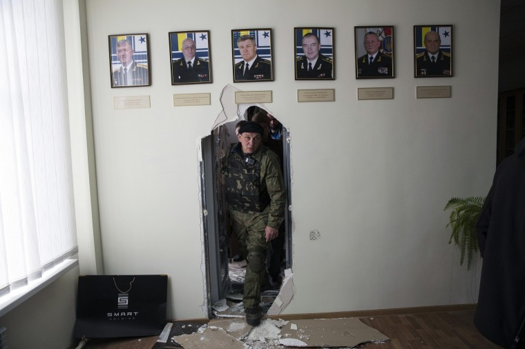 A pro-Russian man looks through a wall after breaking into the territory of the naval headquarters in Sevastopol, in this March 19, 2014 file photo. REUTERS/Baz Ratner