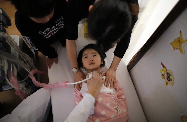 A doctor conducts a thyroid examination on a five-year-old girl as her older brother and a nurse take care of her at a clinic in a temporary housing complex in Nihonmatsu, west of the tsunami-crippled Fukushima Daiichi nuclear power plant, Fukushima prefecture, in this February 27, 2014 file photo. REUTERS/Toru Hanai