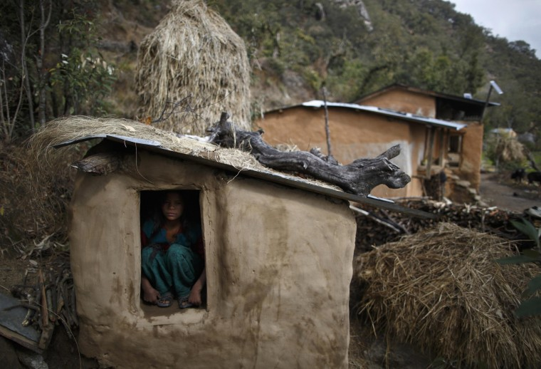 Uttara Saud, 14, sits inside a Chaupadi shed in the hills of Legudsen village in Achham District in western Nepal, in this February 16, 2014 file photo. REUTERS/Navesh Chitrakar/Files
