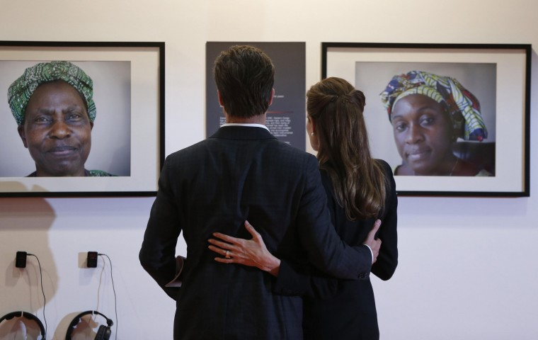 Special Envoy of the United Nations High Commissioner for Refugees, actress Angelina Jolie (R), and her partner actor Brad Pitt, look at photographs of victims of violence at the End Sexual Violence in Conflict summit in London, in this June 12, 2014 file photo. REUTERS/Lefteris Pitarakis/Pool/Files