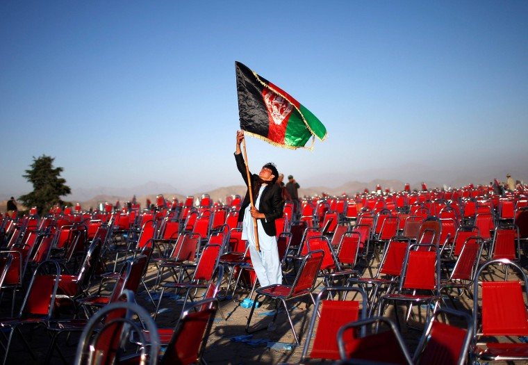 A supporter of Afghan presidential candidate Abdullah Abdullah holds an Afghan flag after an election campaign rally in the Paghman district of Kabul, in this June 9, 2014 file photo. REUTERS/Ahmad Masood