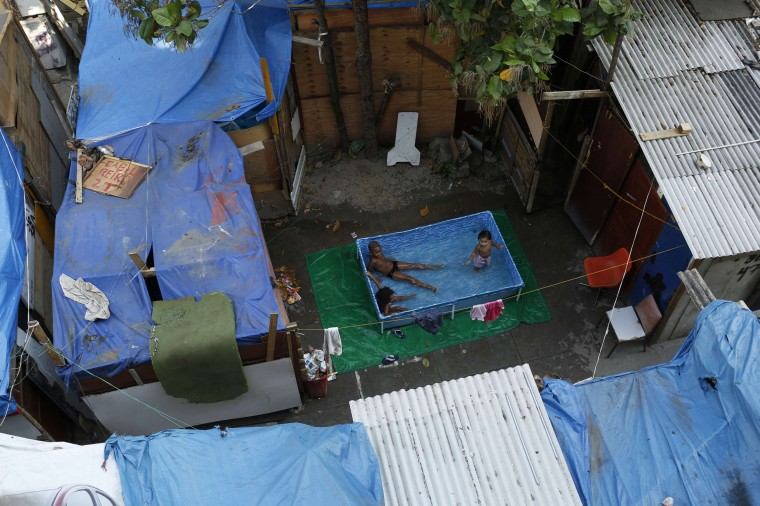 Children sit in a pool among makeshift homes, part of the Nova Tuffy slum, in an abandoned factory compound in Rio de Janeiro, in this October 17, 2014 file photo. REUTERS/Pilar Olivares