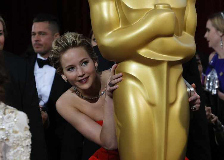 "Jennifer Lawrence, best supporting actress nominee for her role in the film ""American Hustle"", peeks around an Oscar statue on the red carpet as actor Brad Pitt (L) looks on at the 86th Academy Awards in Hollywood, California, in this March 2, 2014 file photo. REUTERS/Adrees Latif"